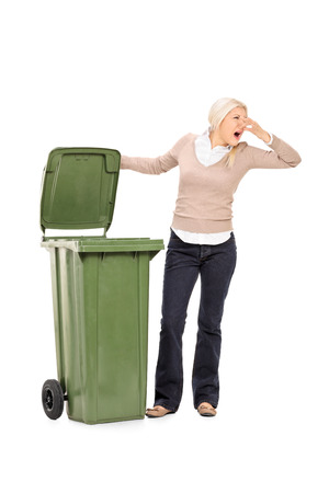 stinky: Vertical shot of a woman opening a stinky trash can isolated on white background Stock Photo
