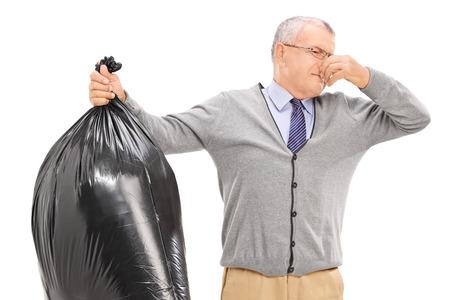 stinky: Senior holding a stinky garbage bag isolated on white background Stock Photo