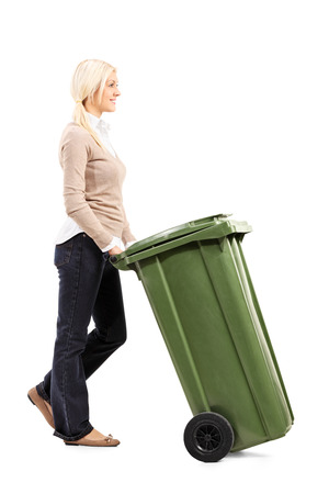 garbage can: Cheerful young woman pushing a garbage can isolated on white background