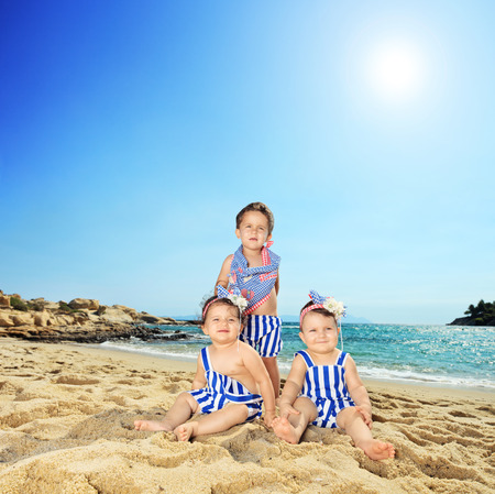 Three cute little toddlers sitting on a tropical beach shot with a tilt and shift lens photo