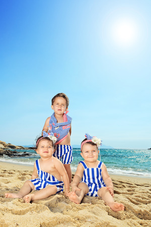 Vertical shot of three cute babies posing on a beach on a sunny summer day photo