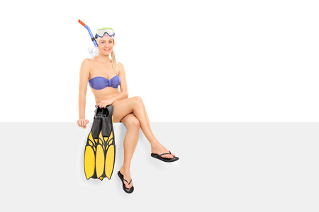 single fin: Woman in bikini holding flippers seated on a panel isolated on white background