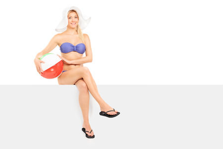 beachwear: Woman in bikini sitting on a panel and holding a beach ball isolated on white background Stock Photo