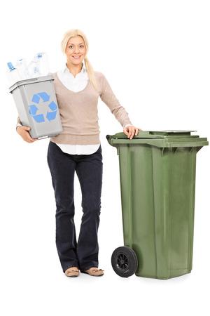 reciclar basura: Retrato de cuerpo entero de una mujer con una papelera de reciclaje y de pie junto a un gran bote de basura aislado en el fondo blanco