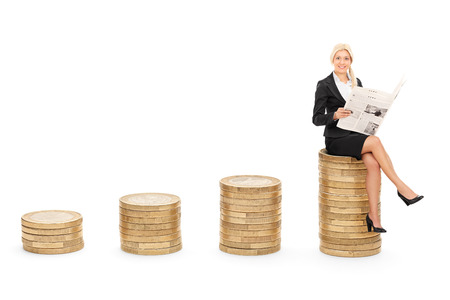 siting: Businesswoman reading the news seated on pile of coins isolated on white background