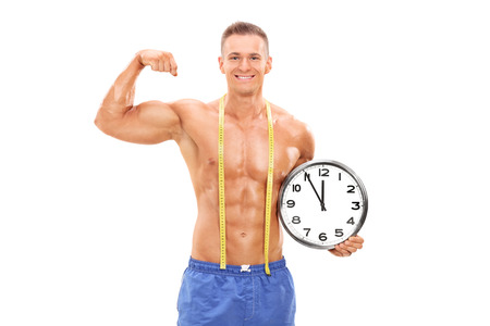 Handsome male athlete holding a big wall clock and flexing his muscle isolated on white background photo