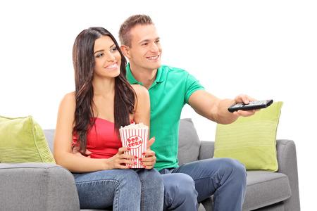 pareja viendo television: Joven pareja viendo la televisión sentado en un sofá aislado en el fondo blanco