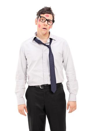 beso labios: Hombre confuso con muchos besos de lápiz labial en su cara aislada en el fondo blanco