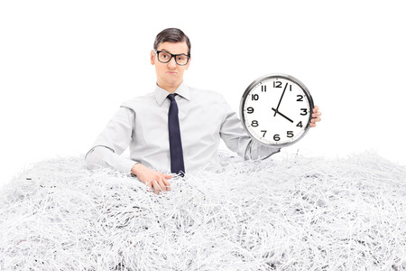 Man holding a clock in a pile of shredded paper isolated on white background photo