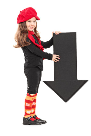 child holding sign: Profile shot of a little girl holding an arrow pointing down isolated on white background