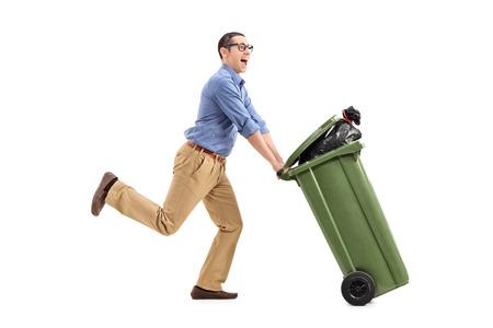 botes de basura: Un hombre excitado empujando un basurero aislado en el fondo blanco Foto de archivo