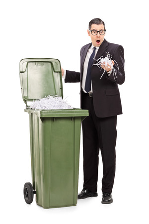 garbage can: Shocked businessman looking into a trash can full of shredded paper isolated on white background Stock Photo