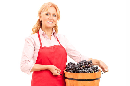 Mature lady holding a bucket full of grapes isolated on white background photo