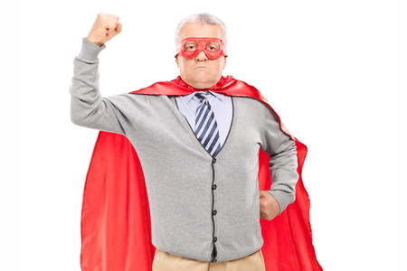 60s adult: Senior in superhero outfit with his fist in the air isolated on white background