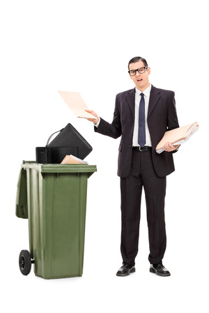 Full length portrait of an angry businessman throwing his stuff in the trash isolated on white background photo