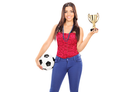 Trendy woman holding a football and a trophy isolated on white background photo