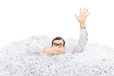 drowning: Studio shot of a man drowning in a pile of shredded paper isolated on white background Stock Photo