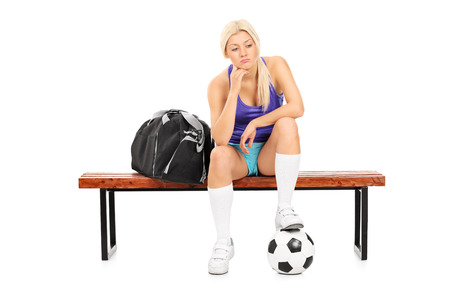 football socks: Worried female football player sitting on a bench isolated on white background Stock Photo