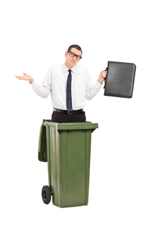 irrelevant: Sad man standing in a trash can and holding a briefcase isolated on white background