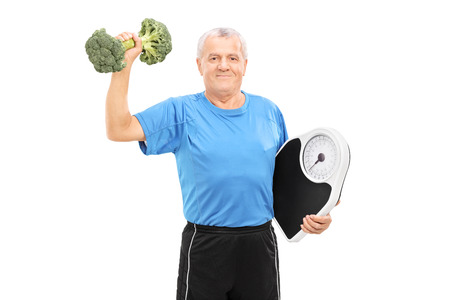 Senior lifting a broccoli dumbbell and holding a weight scale isolated on white background photo
