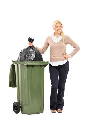 botes de basura: Retrato de cuerpo entero de una mujer joven tirando la basura aislado en el fondo blanco