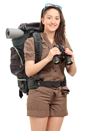 Vertical shot of a female hiker holding binoculars isolated on white background photo
