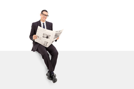 young adult man: Businessman reading the news seated on a panel isolated on white background