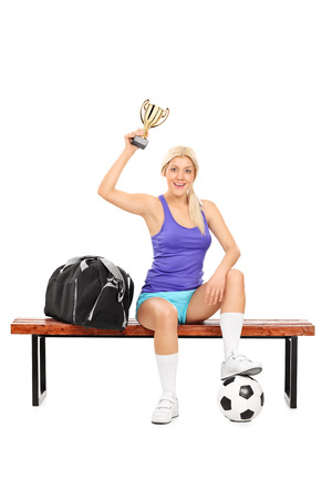 player bench: Female soccer player holding a trophy seated on a bench isolated on white background