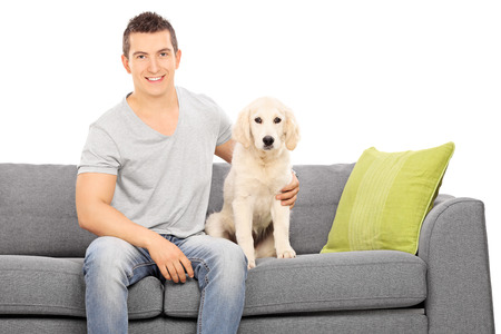 cute guy: Young guy sitting on a sofa with a cute puppy isolated on white background