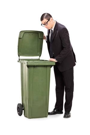 Full length portrait of a businessman looking into a trash can isolated on white background photo