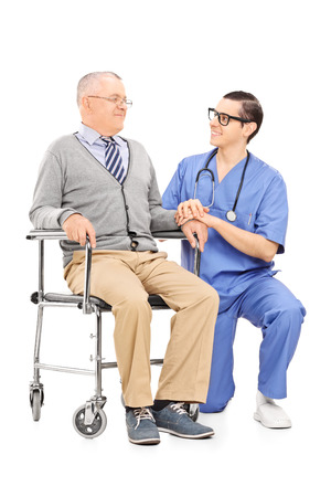 Male nurse talking to a senior patient seated in a wheelchair isolated on white background photo