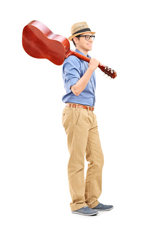Full length portrait of a young guy with an acoustic guitar isolated on white background photo