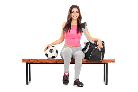 Female football player sitting on a bench with a sports bag next to her isolated on white background photo