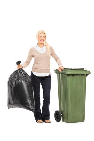 Full length portrait of a woman holding a trash bag next to a garbage bin isolated on white background