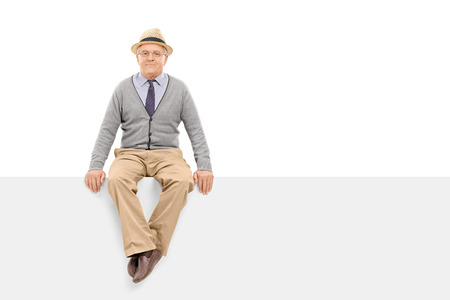old man sitting: Senior gentleman sitting on a blank billboard isolated on white background