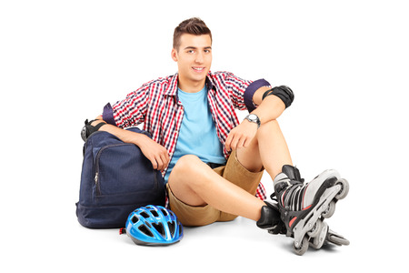 Young man with roller blades sitting on the floor isolated on white background photo