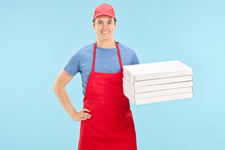 Pizza chef holding a bunch of boxes on blue background photo