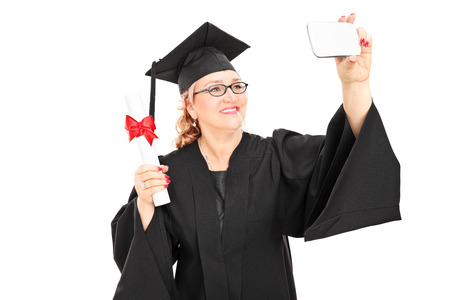 Mature female graduate taking a selfie with cell phone isolated on white background photo