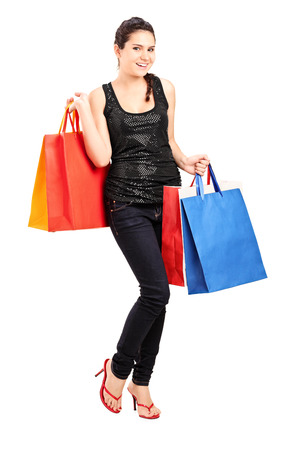 Full length portrait of a fashionable female holding bunch of shopping bags isolated on white background photo