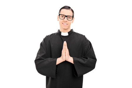 reverent: Studio shot of a young priest praying and looking at the camera isolated on white background