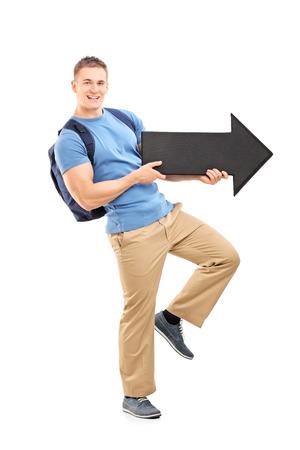 flecha direccion: Retrato de cuerpo entero de un estudiante masculino que sostiene una gran flecha apuntando hacia la derecha negro aislado en fondo blanco Foto de archivo