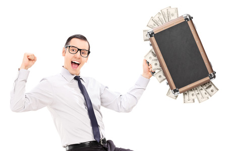 Overjoyed businessman holding a briefcase full of money isolated on white background photo