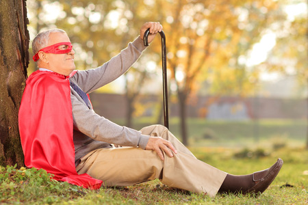 Senile old man sitting outdoor in a superhero costume Imagens
