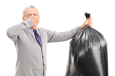 stinky: Senior carrying a stinky garbage bag isolated on white background Stock Photo