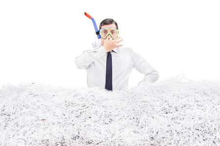 shredding: Businessman diving into a pile of shredded paper isolated on white background