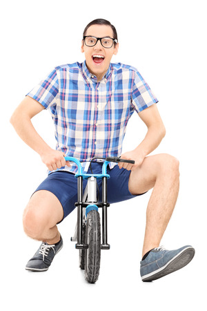 Silly young man riding a small childish bike isolated on white background Reklamní fotografie