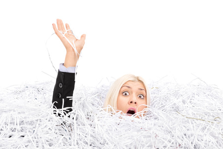 Businesswoman drowning in a pile of shredded paper isolated on white background Stock Photo