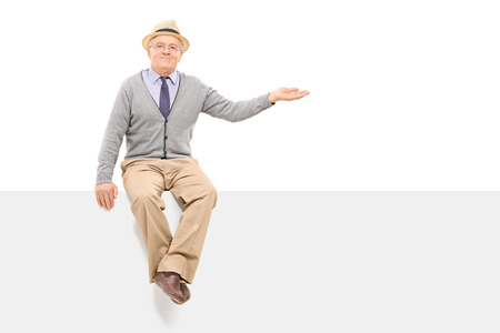 Senior gesturing with hand seated on a blank panel isolated on white background Stock Photo
