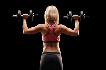 Female bodybuilder exercising with weights on black background, rear view photo