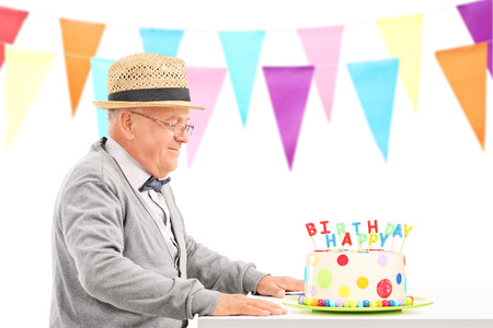 old man happy: Happy senior sitting at a table with birthday cake isolated on white background